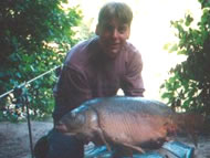 Man holding a 18lb 9oz mirror carp in front of Normanhurst lake