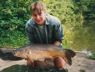 Man holding a 20lb 6oz mirror carp in front of Normanhurst lake