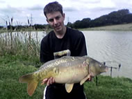 Young man holding a mirror carp