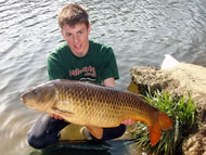 Man crouching in the lake holding a common carp